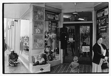 Woman, boy and man near entrance to store.