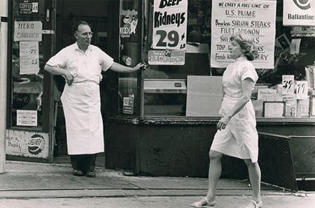 Man in doorway. Woman walking down sidewalk