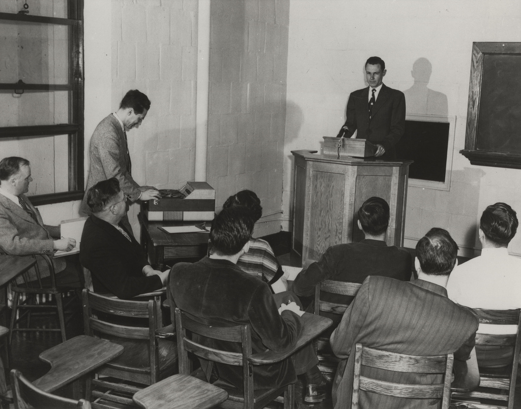 Divinity student delivers practice sermon before faculty and students, undated