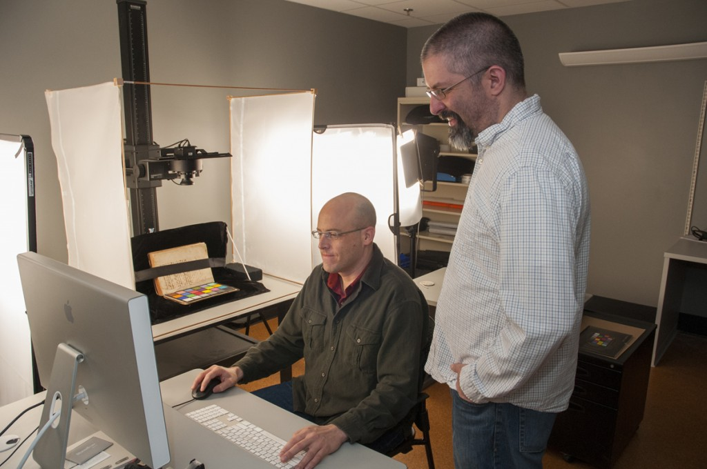 Digital Production Center, Perkins Library: Digitization Specialist Alex Marsh (left) and Mike Adamo, Lead Digitization Production Developer, prepare to digitize an early Arabic manuscript from the Rubenstein Rare Book & Manuscript Library. Once complete, high-resolution scans of the historical document will be available online.