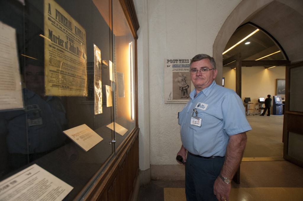 Rubenstein Library, Outside Rare Book Room: Robert Autry, a licensed locksmith who works in the Facilities Management Key and Lock Shop, pauses to look at an exhibit on broadsides from the Rubenstein Library. Autry is in charge of keeping doors and locks in working order all over campus, including card readers, vault locks, file cabinets, building keys, and other secure access points throughout the Libraries.