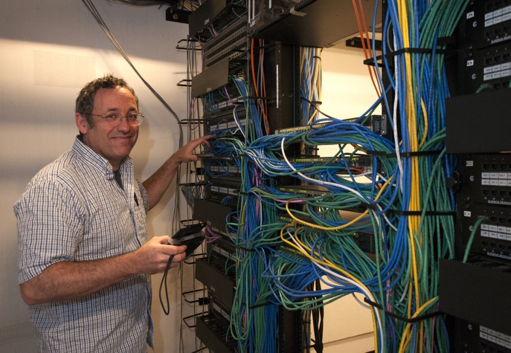 Electrical Closet, Perkins Library: Desktop Support Analyst Paul Wilshire works on the Ethernet circuits that provide wired and wireless internet access throughout Perkins and Bostock Libraries.