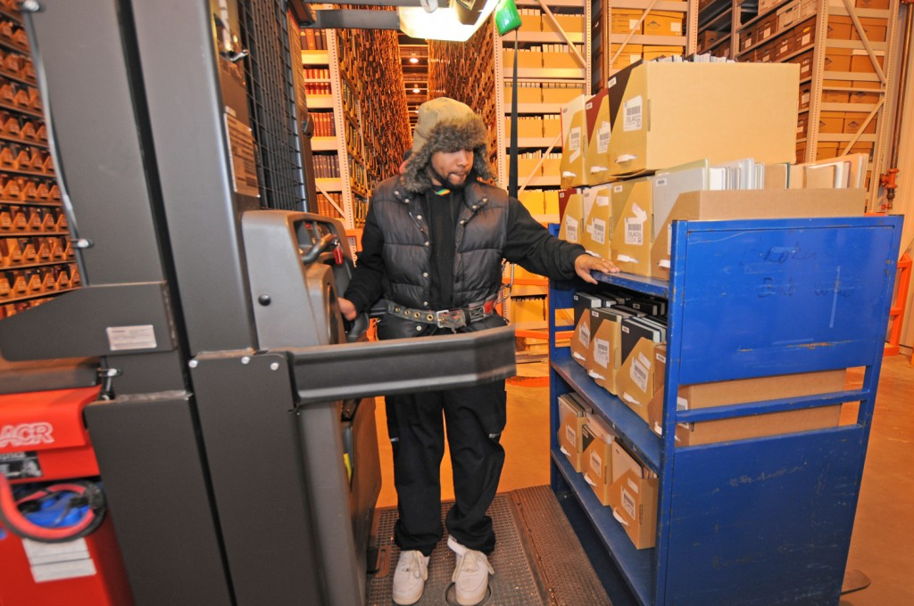 Library Service Center: Daniel Walker, Library Assistant, uses a special lift to retrieve and shelve items at Duke's high-density, off-site repository. Each of the facility's massive shelves is three stories tall and almost a football field long. The air inside is kept at a constant 50 degrees Fahrenheit with 30 percent humidity, ideal conditions for preserving books and paper. At full capacity, the Library Service Center could accommodate nearly nine million volumes—more than all the materials in Duke's ten libraries combined.