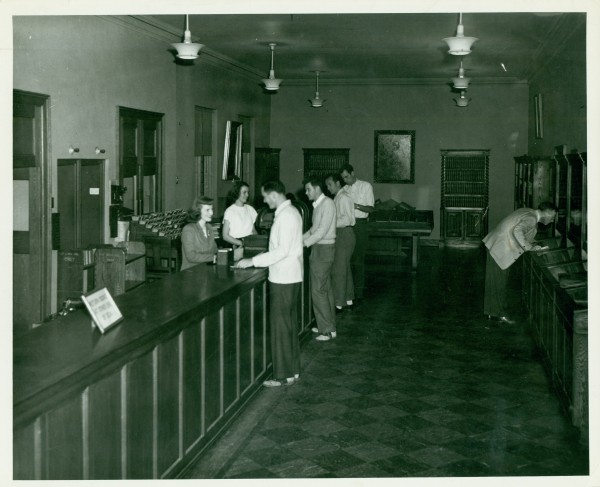 The General Library circulation desk in the 1940s, showing double booklift doors (and indicator lights) at left.