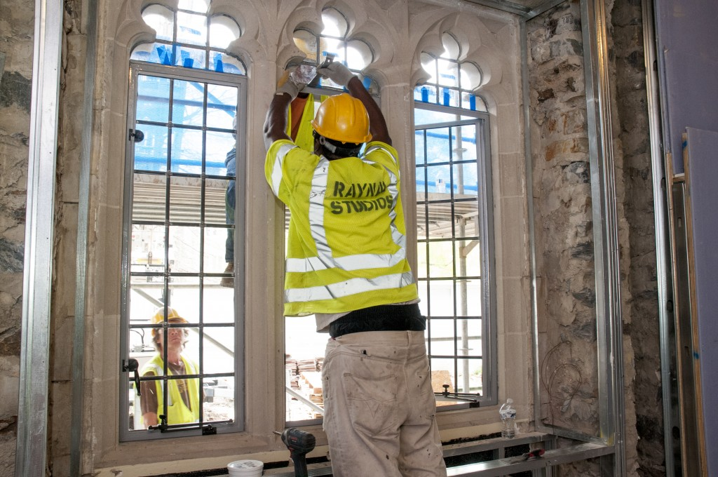 April 2014: Workers install the refurbished leaded-glass windows that were removed at the beginning of the renovation and shipped to Virginia for professional restoration. For more about the window restoration project, see our story in this issue.