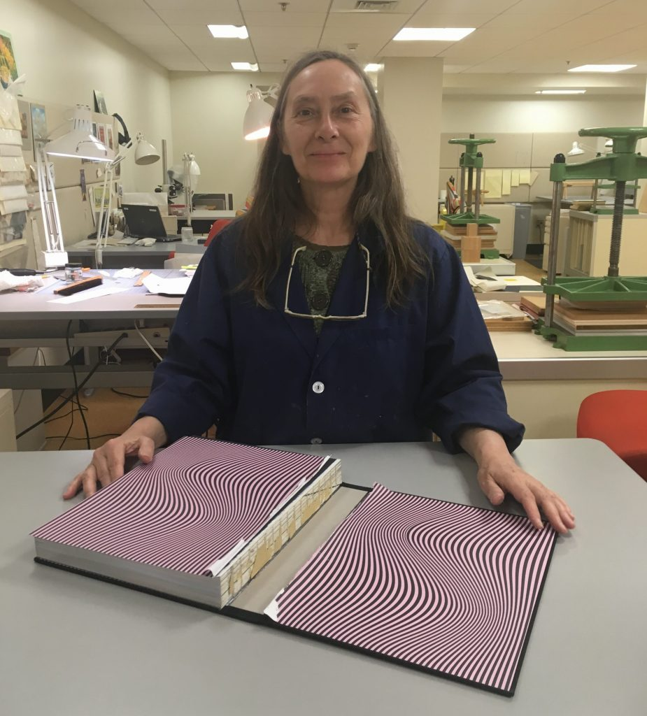 Mary Yordy displays a damaged case binding, ready for repair.