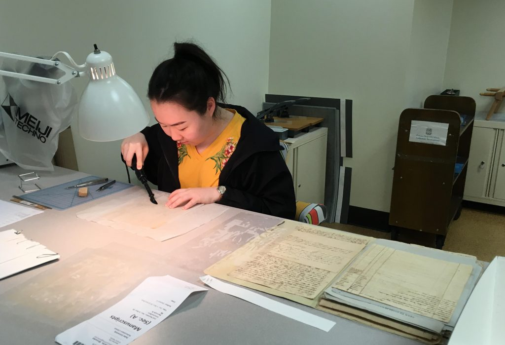 Helen Lee mends manuscript material ahead of digitization.