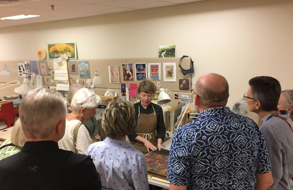 Conservator Erin Hammeke describes the conservation treatment of a very large book to seven tour attendees.