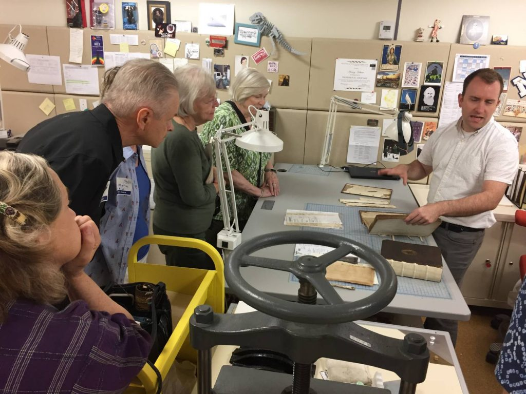 Conservator Henry Hebert shows two bindings undergoing treatment to six tour attendees.