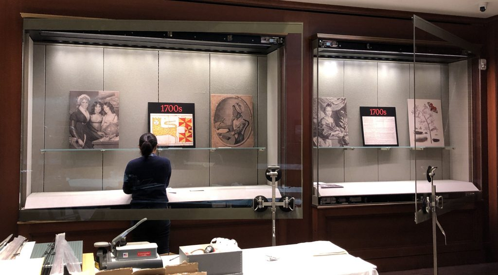 Open exhibit cases with reproduction images placed on shelves.