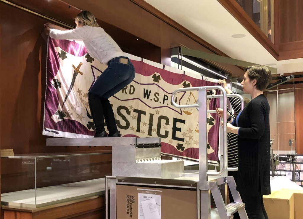 Grolier Club and Duke Library staff hanging a large reproduction banner