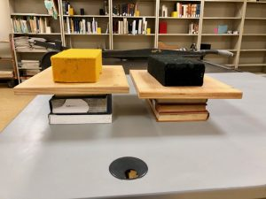 books pressing under a brick