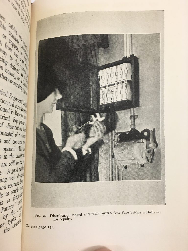 Photomechanical print of a woman repairing a fuse box.