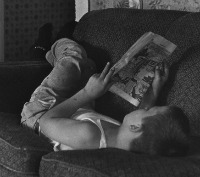 Boy lying on couch, reading comics. From the William Gedney Photographs and Writings, 1950s-1989.