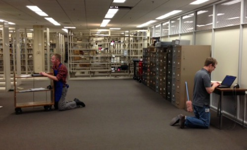 Joshua Larkin Rowley and Noah Huffman: too busy checking materials into our new stacks to find a chair.