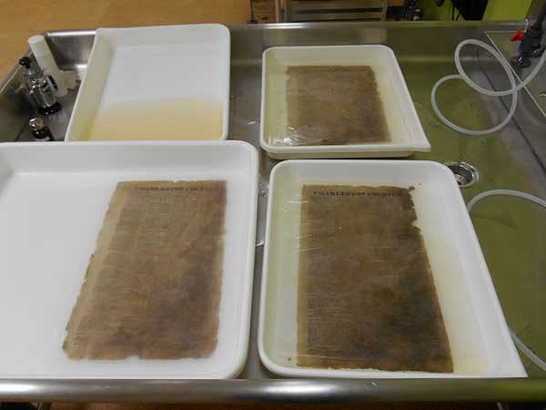 Aqueous treatment to remove discoloration and degradation products.  The upper left tray shows the extent of discoloration removed from a page in its first bath.