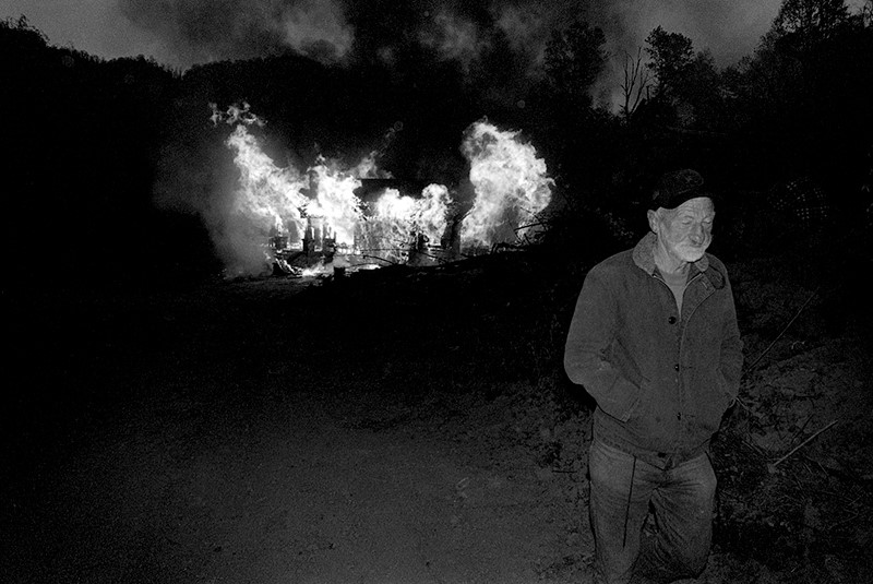 J.D. Thomas walking away from his burning home place, Sprinkle Creek, Madison County, N.C., 1997. Copyright, Rob Amberg