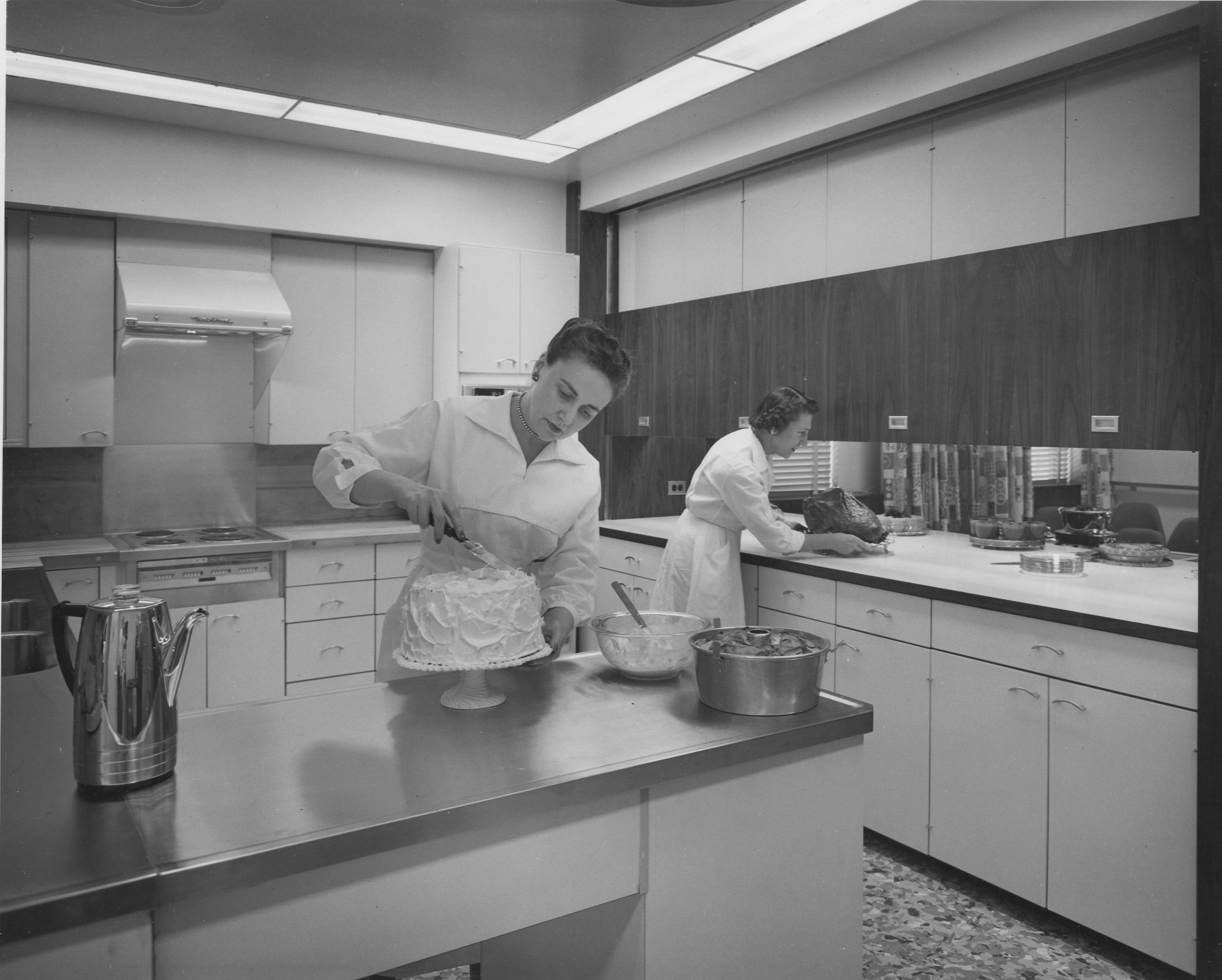 Two women in the JWT Chicago Office Test Kitchen. One is icing a cake, the other is in the background preparing a turkey.