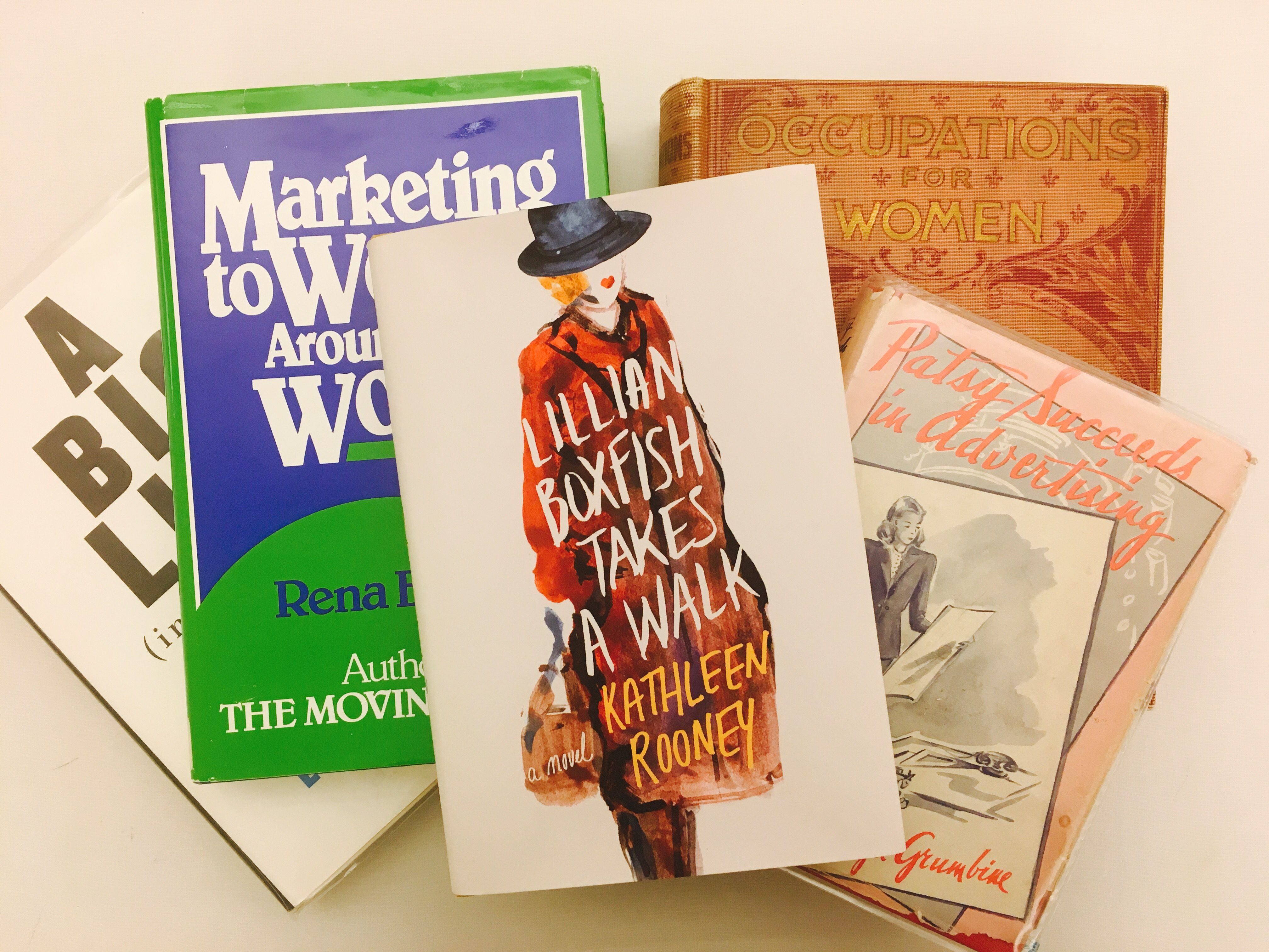 "Photograph of a stack of 5 books related to women in the advertising industry. ""Lillian Boxfish Takes a Walk"" is on the top"