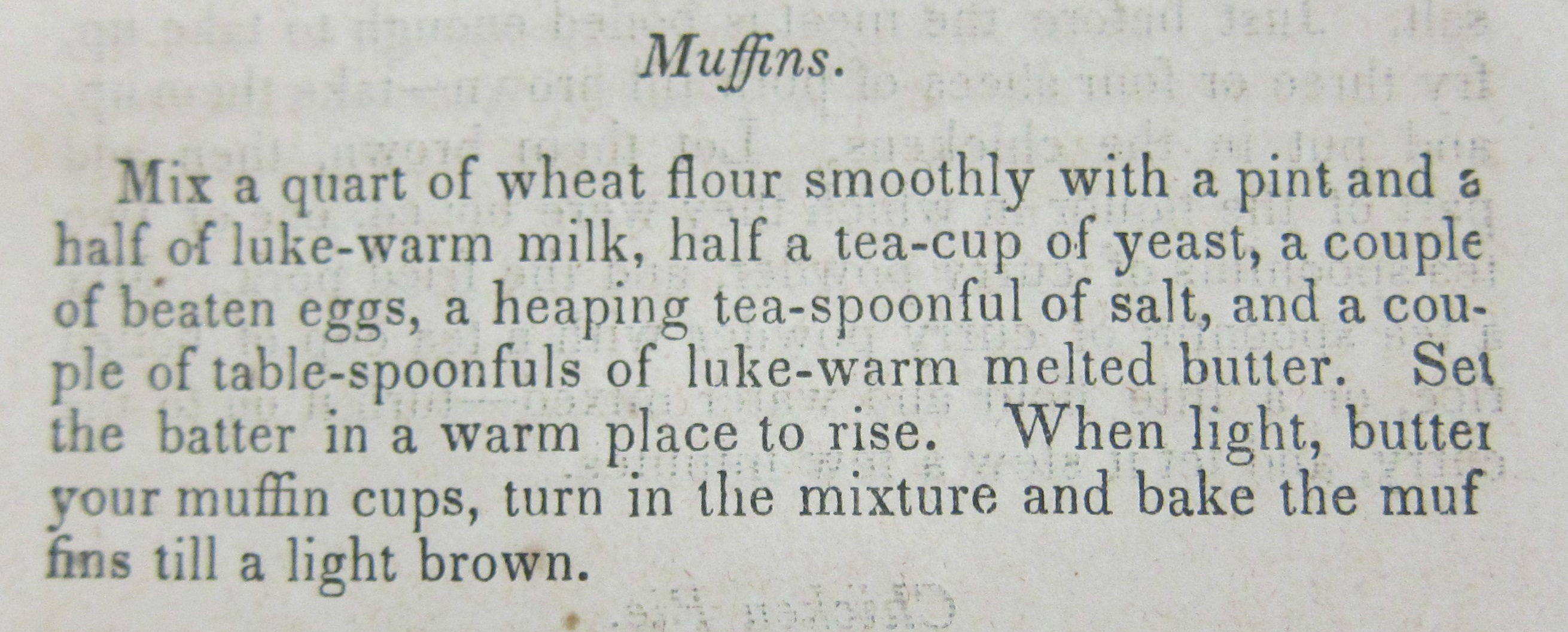 Image of recipe in book. It reads: Mix a quart of wheat flour smoothly with a pint and a half of luke-warm milk, half a tea-cup of yeast, a couple of beaten eggs, a heaping tea-spoonful of salt, and a couple of table-spoonfuls of luke-warm melted butter. Set the batter in a warm place to rise. When light, butter your muffin cups, turn in the mixture and bake the muffins till a light brown.