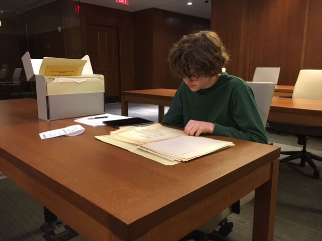 Photo of Benjamin Knight working with a box from the Oscar Morgenstern papers in the Rubenstein Library reading room.