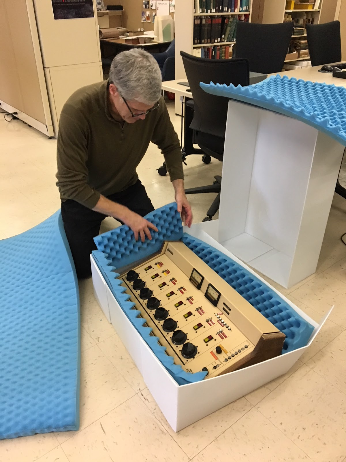 Archivist kneeling over a large box with the soundboard inside.