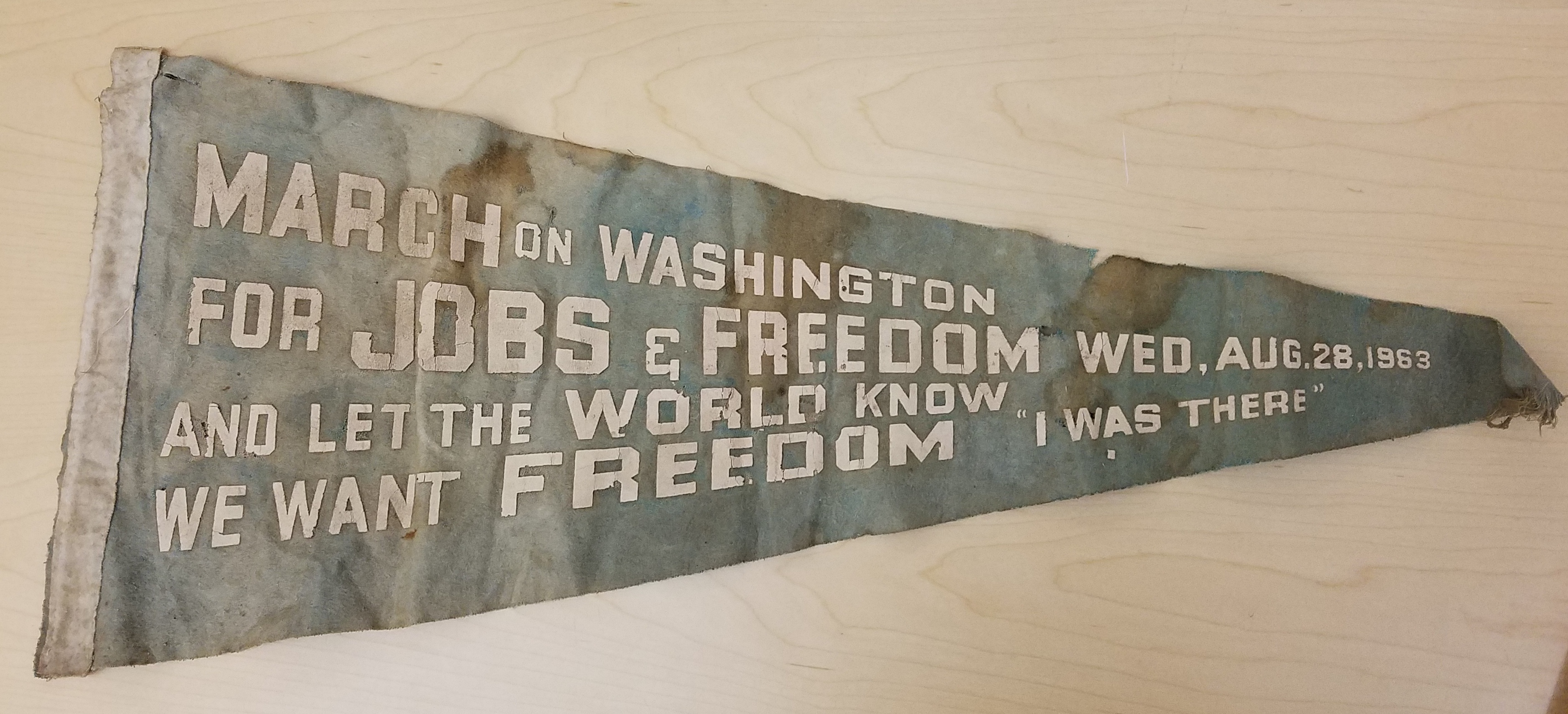 Faded and worn cloth pennant with the words March on Washington for Jobs and Freedom and Let the World Know We Want Freedom