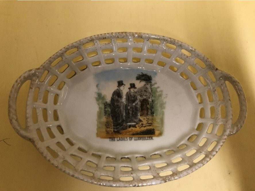 Painting of Ladies of Llangollen on the porcelain, showing ladies in dark clothes and top hats.