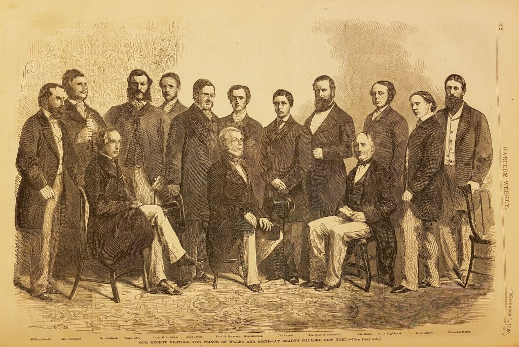 "Wood engraving of 14 men dressed in 19th century suits with long jackets. Three are seated in chairs, the others standing. The image is captioned ""The Prince of Wales and Suite"""