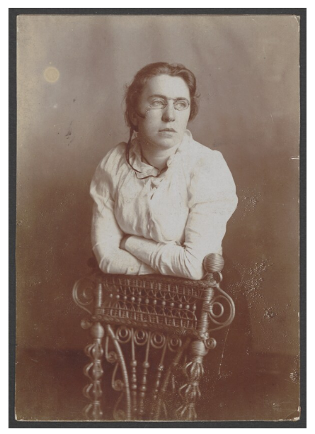 A white woman, Emma Goldman, is phtographed from the waist up, leaning against the back of a chair. She is wearing pince-nez glasses and looking away from the camera to the right.