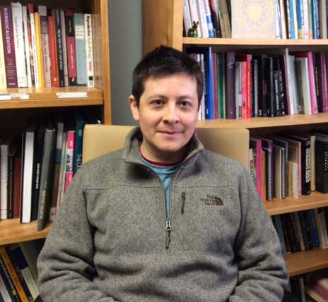 Photo of Dr. Raul Necochea in his office, with bookshelves behind him.