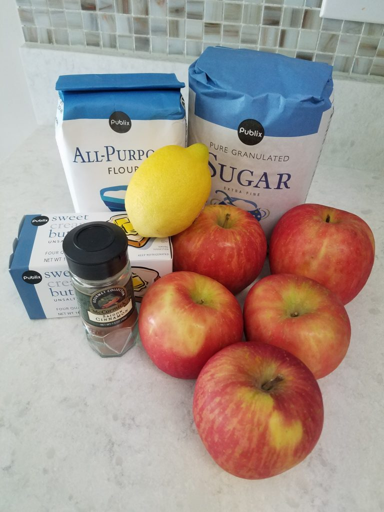 Image showing ingredients used for apple pie: a bag of flour, a bag of sugar, a carton of butter, a jar of cinnamon, a lemon, and five apples