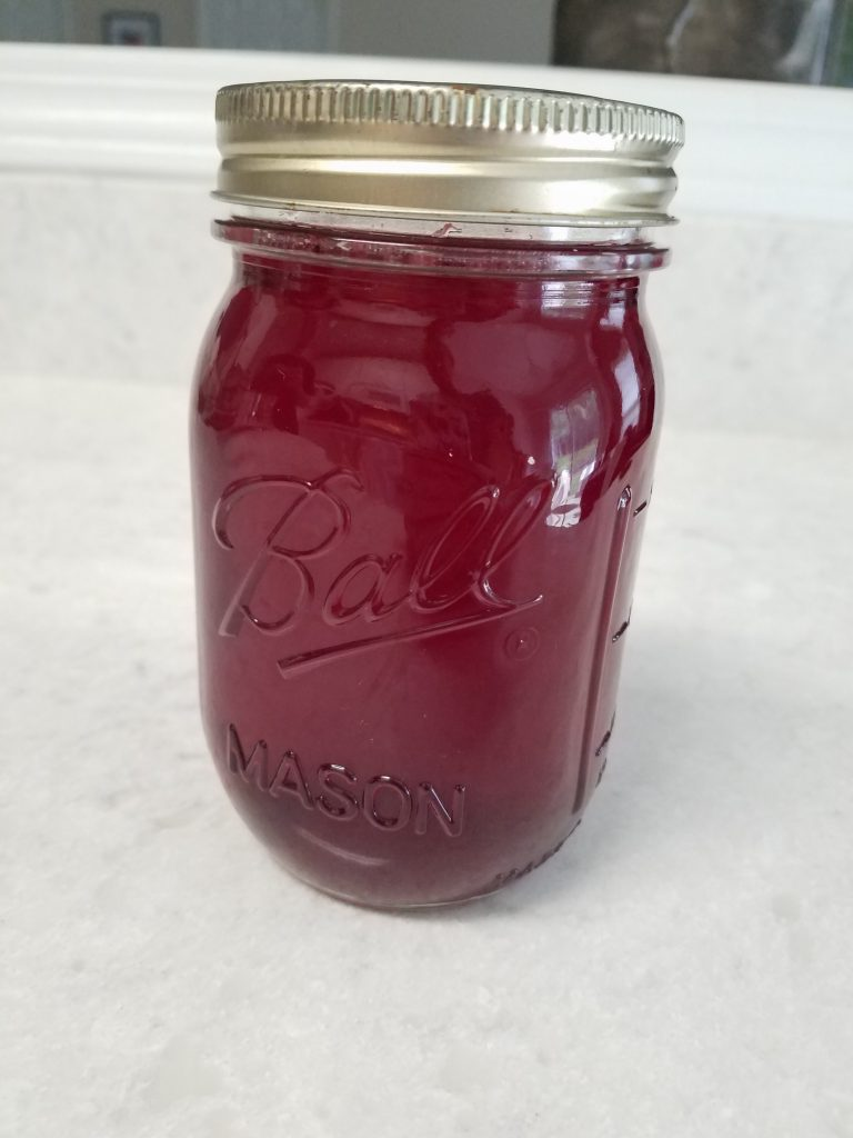 photograph of raspberry shrub in a glass mason jar. the liquid in the jar is a dark red.