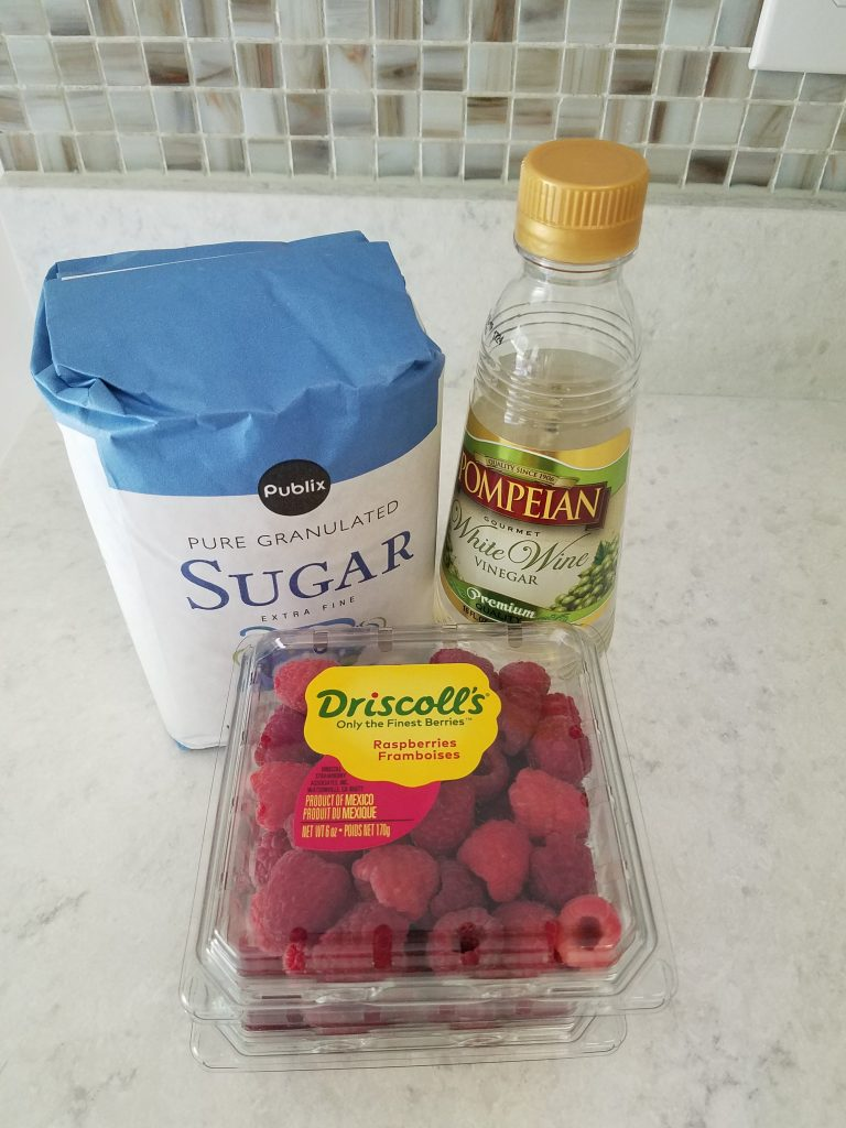photograph of ingredients for raspberry shrub on kitchen counter: a bag of sugar, a bottle of white wine vinegar, and a carton of red raspberries