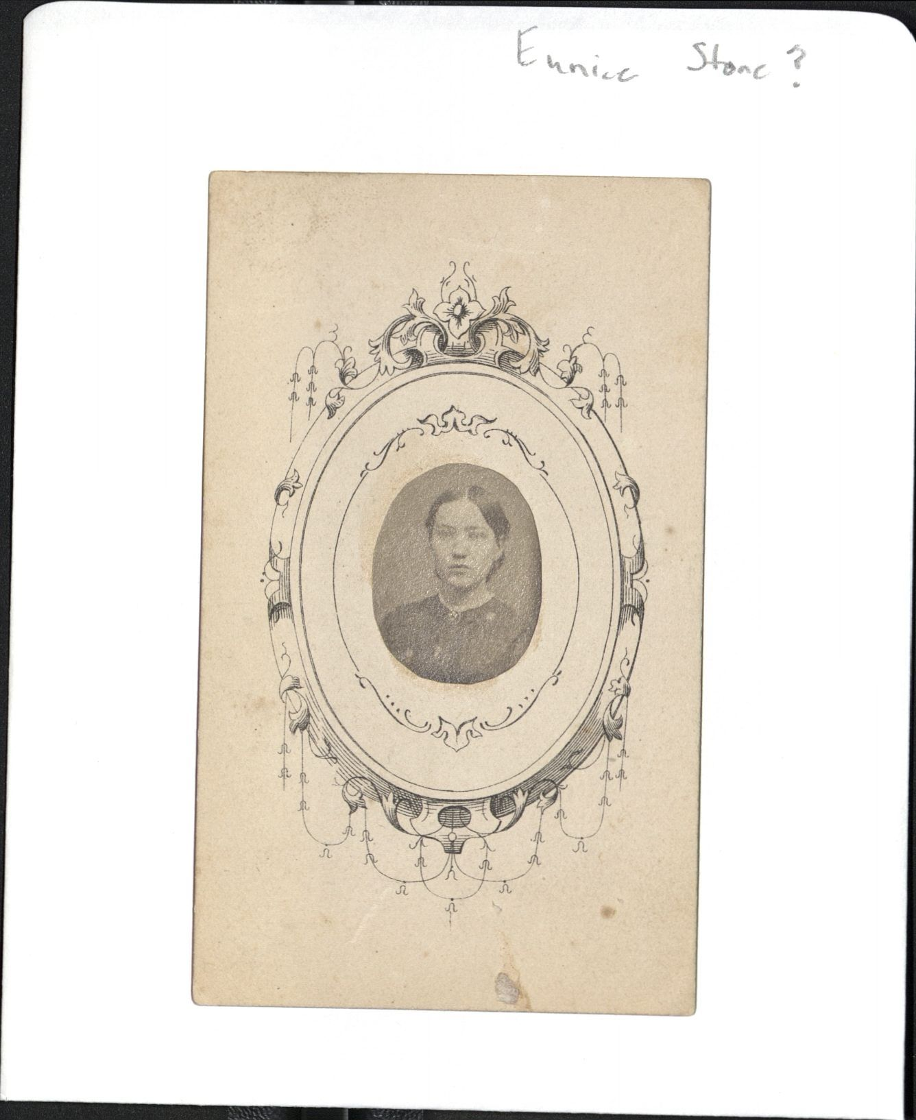 Small 19th century black and white photo of a woman pasted on a decorated card.