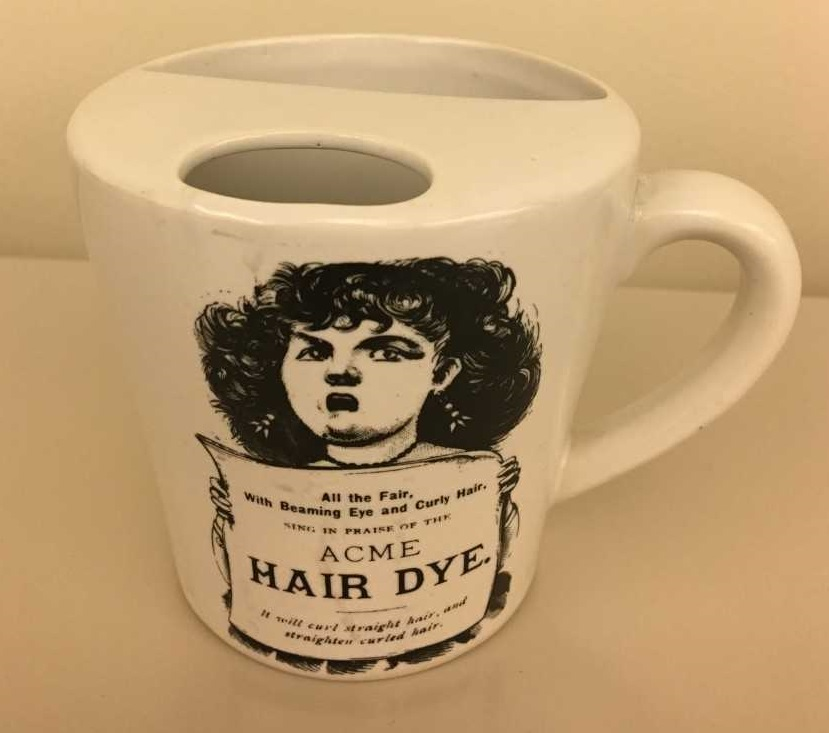 Photograph of a mustache cup. It is a mug with a semicircular ledge inside. The ledge has a half moon-shaped opening to allow the passage of liquids and serves as a guard to keep moustaches dry. The side of the mug features an advertisement for Acme Hair Dye.