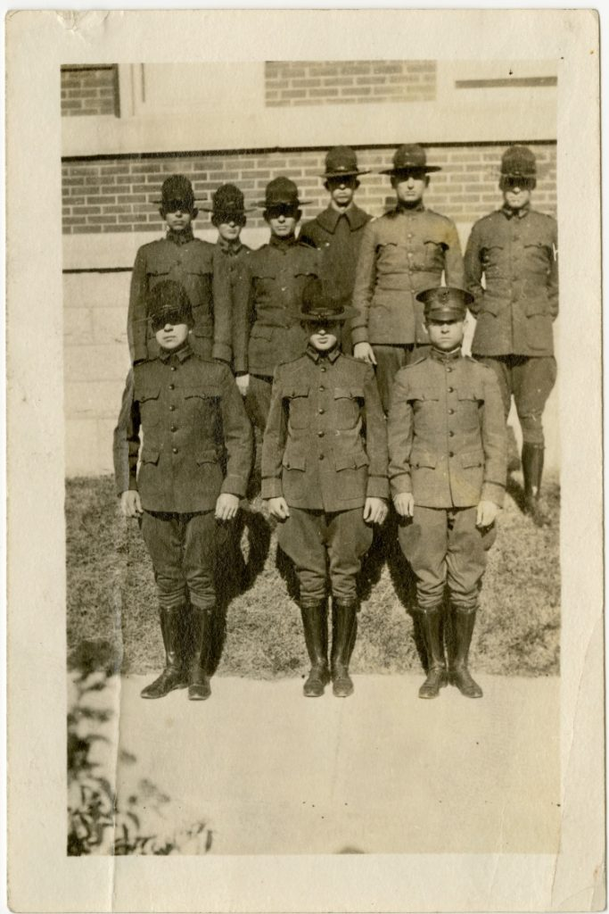 Black and white photograph of nine young men in Army uniforms, standing in two rows. A brick building is a background.
