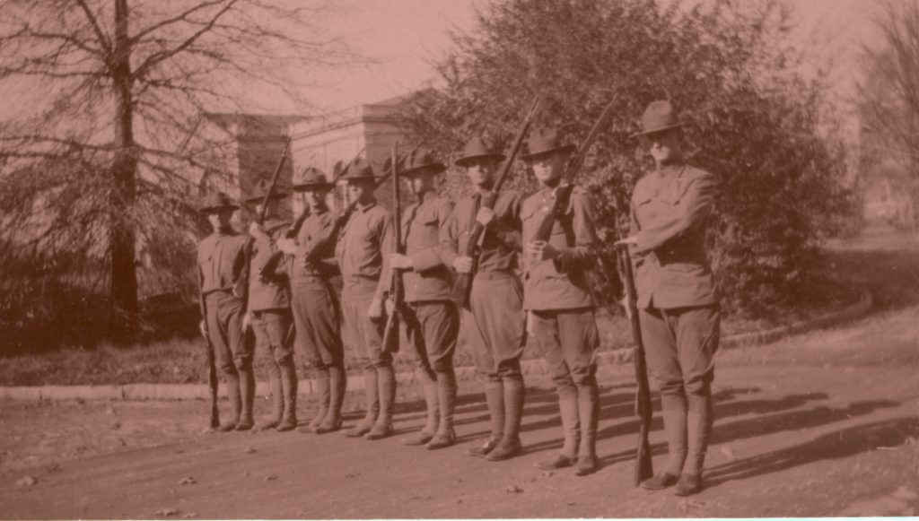 Black and white photograph of young men in Army uniform. They are standing in a line together, holding rifles. A building on Duke's East Campus is in the backgroun
