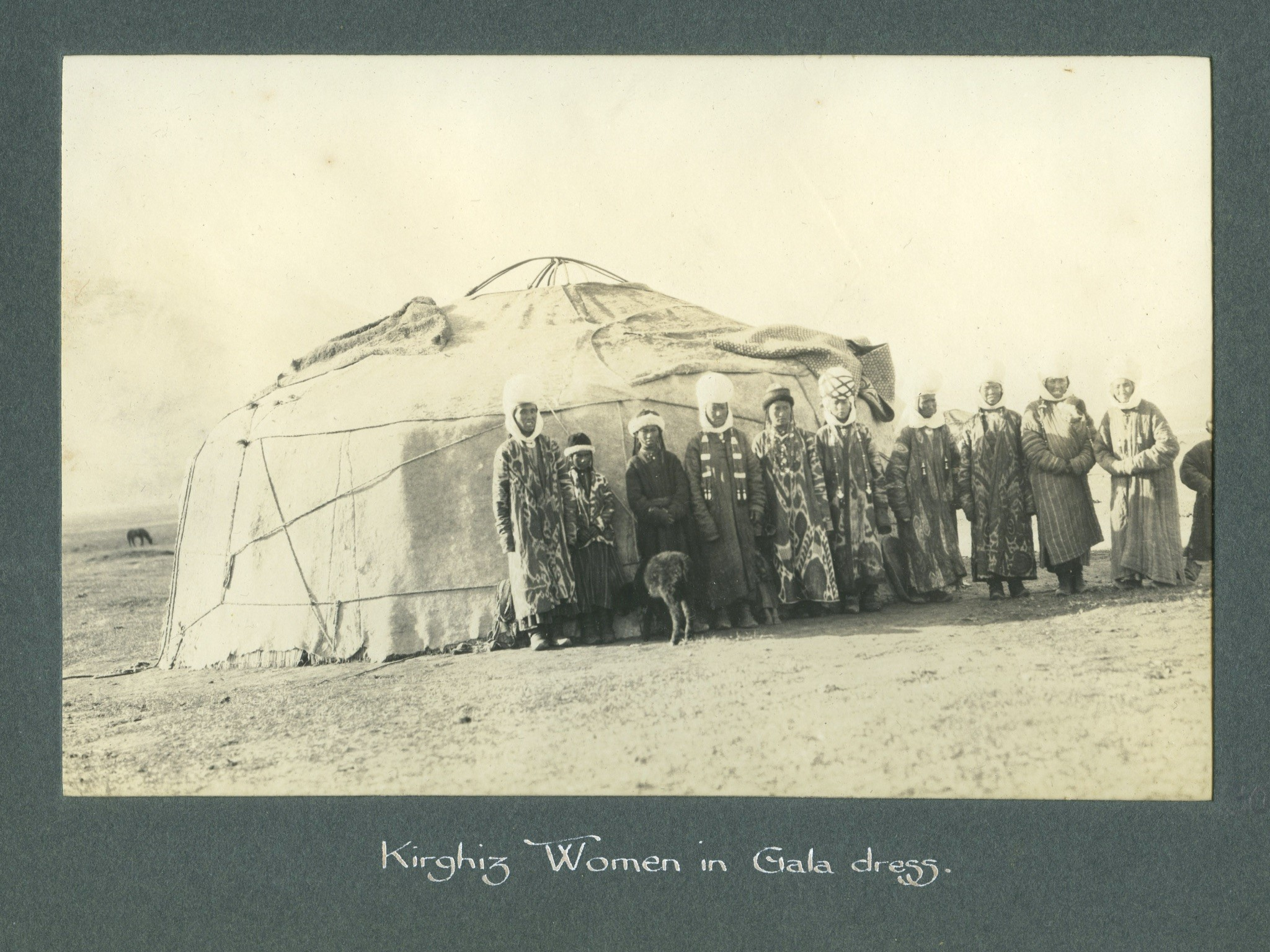 Kirghiz women standing together in front of a yurt.