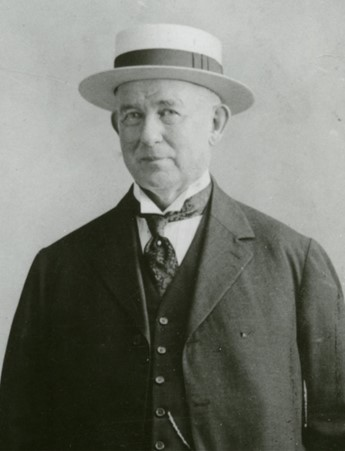 Portrait photo of James Buchanan Duke in a boater hat.