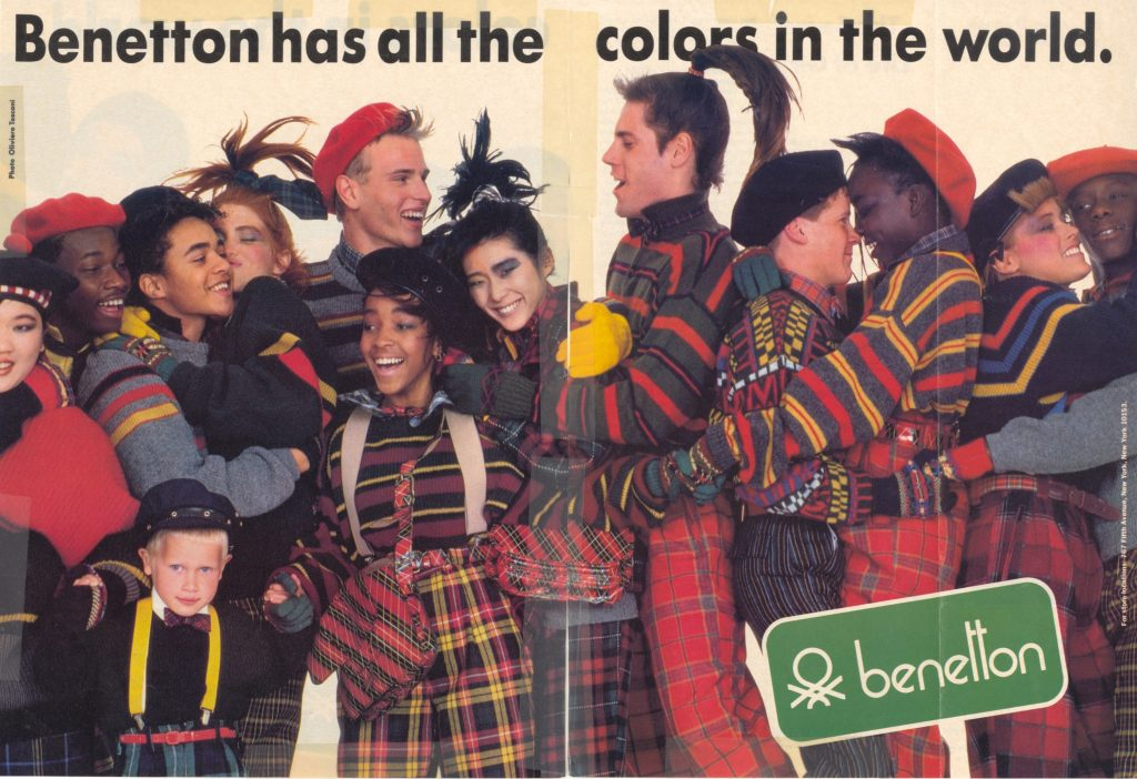 Benetton magazine advertisement featuring about a dozen people of different races and ages. They are all wearing Benetton clothing and hugging one another.