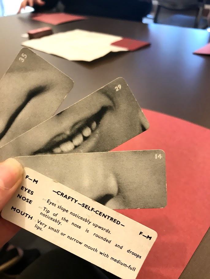 "Photo of someone's hand holding four cards. One with a nose on it and two with a mouth, and a fourth with a description of a ""crafty - self-centered"" face."