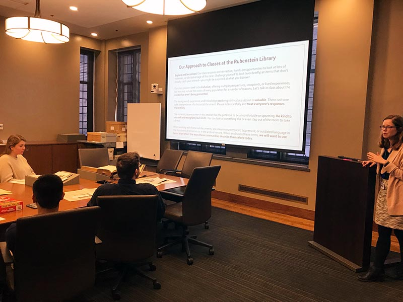 Color photograph of librarian teaching the code of ethics to a class session. The code appears projected on a screen behind her. Students sit at a conference table in front of the screen.