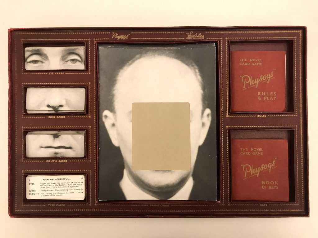 Photograph of the Physogs game box with the lid off. In the center is a stack of cards with a head with a blank space for the face. On the left are four sets of cards, one of eyes, one of noses, one of mouths, and one of descriptions of facial features. Instruction booklets are on the right.