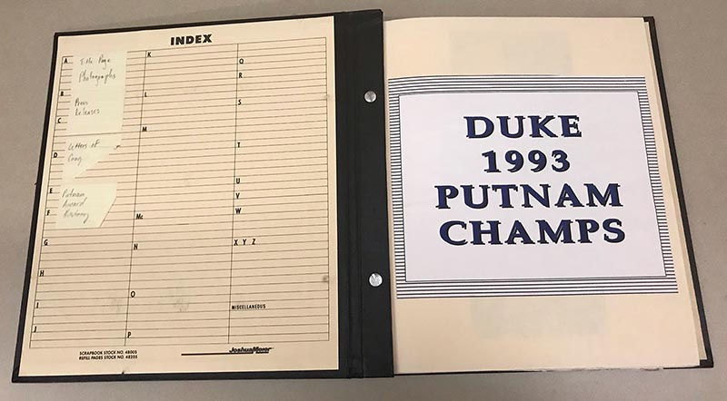 "The inside front cover of the Putnam scrapbook. The right-hand page reads ""Duke 1993 Putnam Champs in blue capital letters."