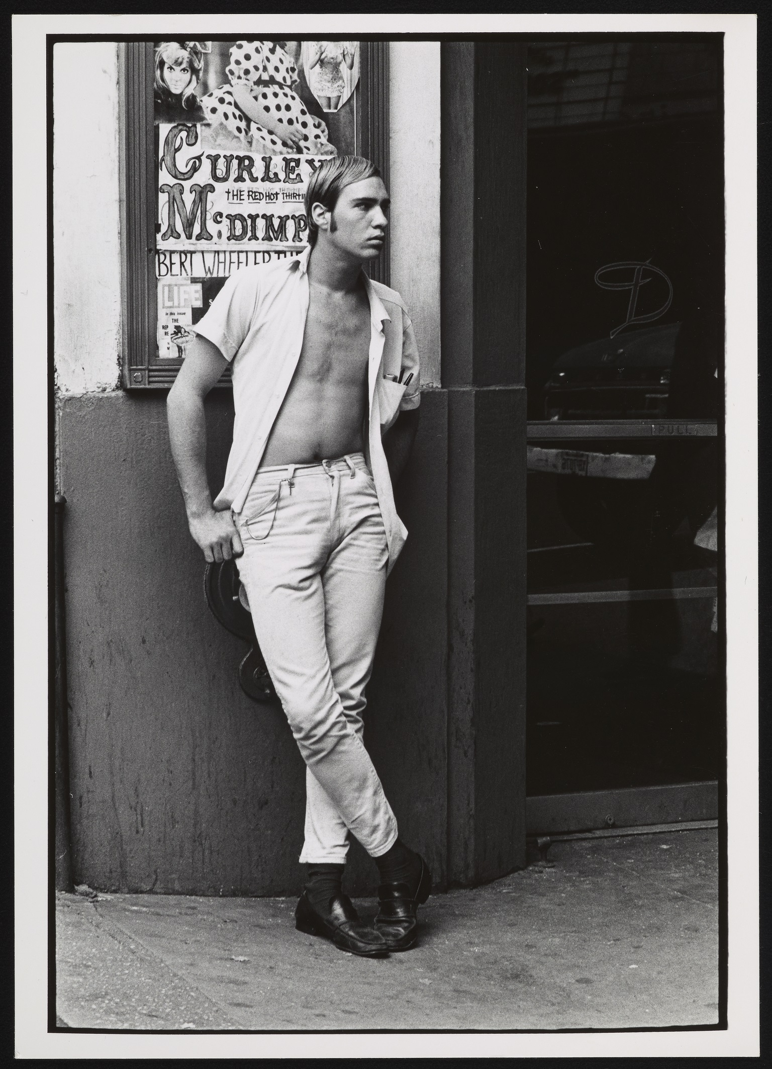 Man with unbuttoned shirt standing on street near strip club.