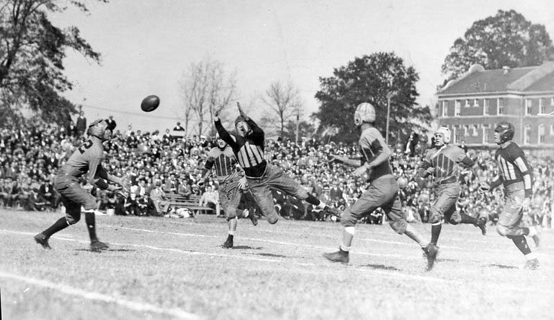 A player heroically dives for the ball during a game in the 1920's.