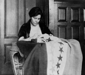 black and white photograph showing a white woman with a large swath of fabric with stars on it drapped over her lap.
