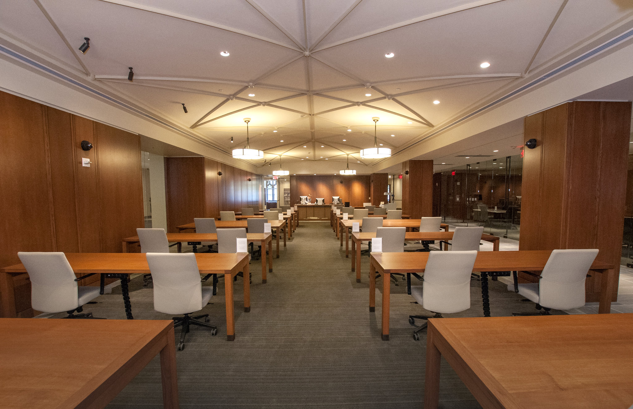 The reading room of the David M. Rubenstein Rare Book & Manuscript Library, taken from the back. Two columns of tables and chairs lead to the reference desk and reading room doors. The walls are wood paneled and the ceilings are vaulted.