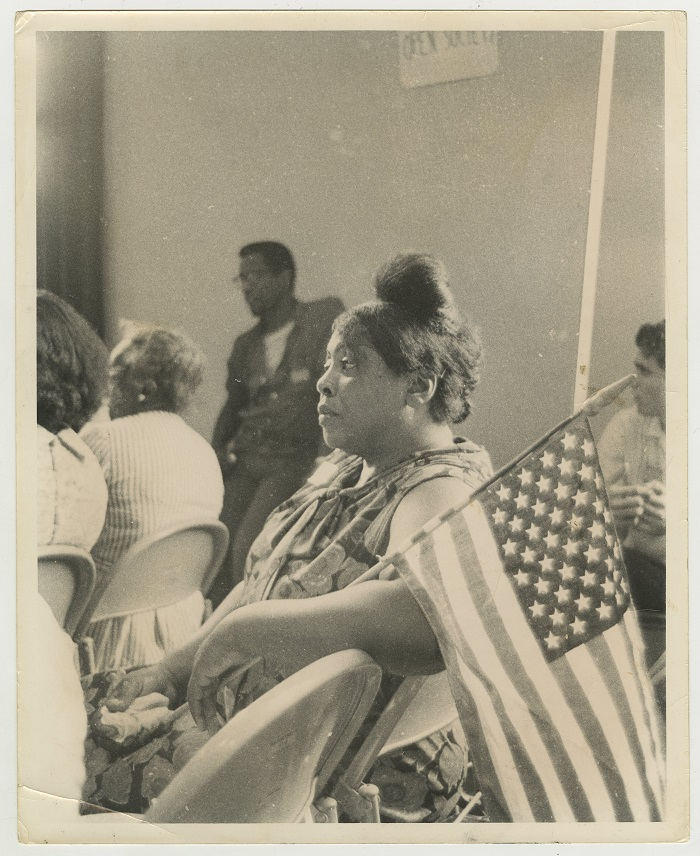 A black and white photo showing Fannie Lou Hamer seated at an event holding an American flag.